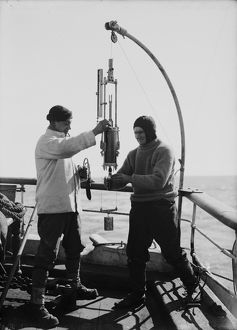 Edward Nelson and Dennis Lillie taking sample from bottle. January 1st 1911