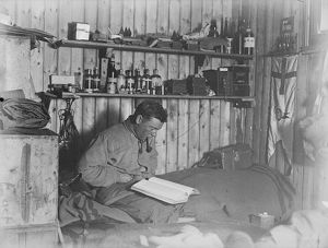 George Murray Levick seated on his bunk, reading
