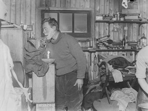 George Murray Levick shaves by candlelight in the hut