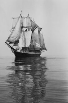 Penola at sea with sails set, reflections in foreground