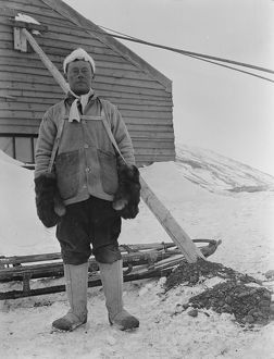 Portrait of George Murray Levick beside a sledge and hut