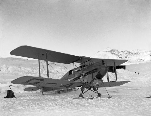 Photographer: Cozens, Henry Iliffe (1904-1995). Expedition: British Arctic Air Route Expedition 1930-31. Leader: Henry George (Gino) Watkins. Date: 1930. A De Havilland Moth biplane on skis sits on ice. Snow-covered mountains in background
