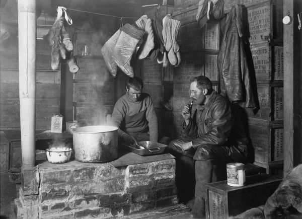 "Photographer:Ponting, Herbert (1870-1935)  Location:Scott Polar Research Institute, University of Cambridge  Expedition:British Antarctic Expedition 1910-13  Date:1911  Cecil Meares and Dimitri Geroff at the blubber stove in the ""Discovery"" Hut at Hut Point"