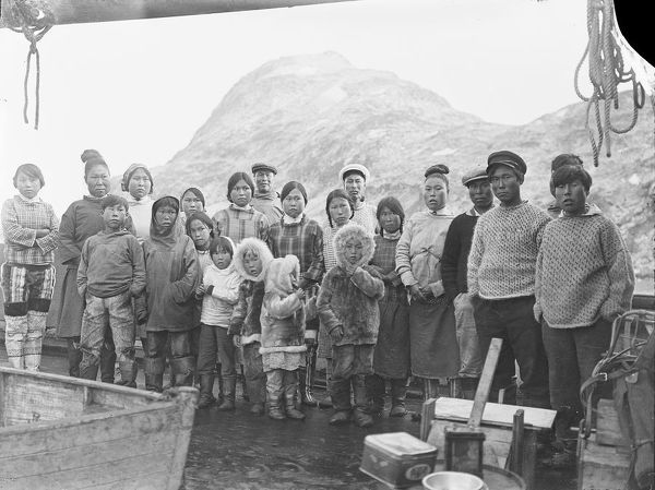 Photographer: Cozens, Henry Iliffe (1904-1995). Expedition: British Arctic Air Route Expedition 1930-31. Leader: Henry George (Gino) Watkins. Date: 1930. Group of Inuit men, women and children, some in traditional clothing, pose for camera on the deck of the ship 'Quest'