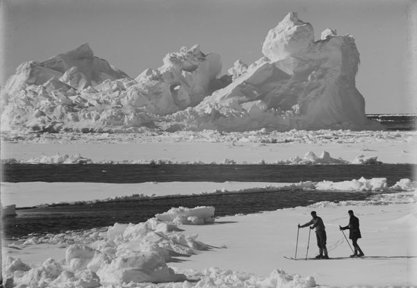 Photographer:Ponting, Herbert (1870-1935)  Location:Scott Polar Research Institute, University of Cambridge  Expedition:British Antarctic Expedition 1910-13  Date:1910  Iceberg in pack ice. Frank Debenham and T. Griffith Taylor on the ice