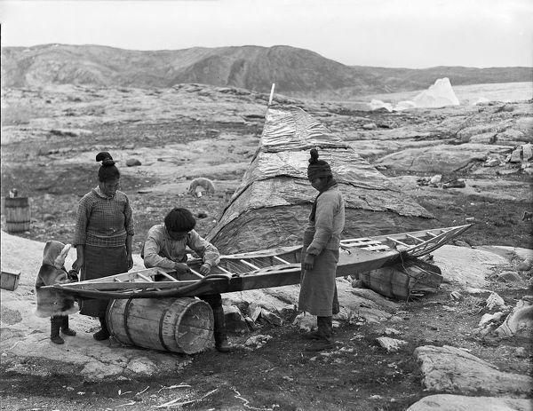 Photographer: Cozens, Henry Iliffe (1904-1995). Expedition: British Arctic Air Route Expedition 1930-31. Leader: Henry George (Gino) Watkins. Date: 1930. An Inuit man sits sewing seal skin onto the wooden frame of a kayak. The kayak is supported on two barrels